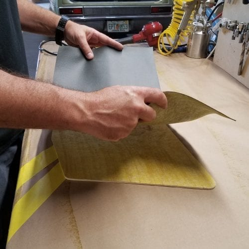 man's hands placing upholstery material on panel