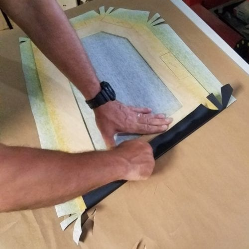 folding and wrapping first side of upholstery on trunk panel
